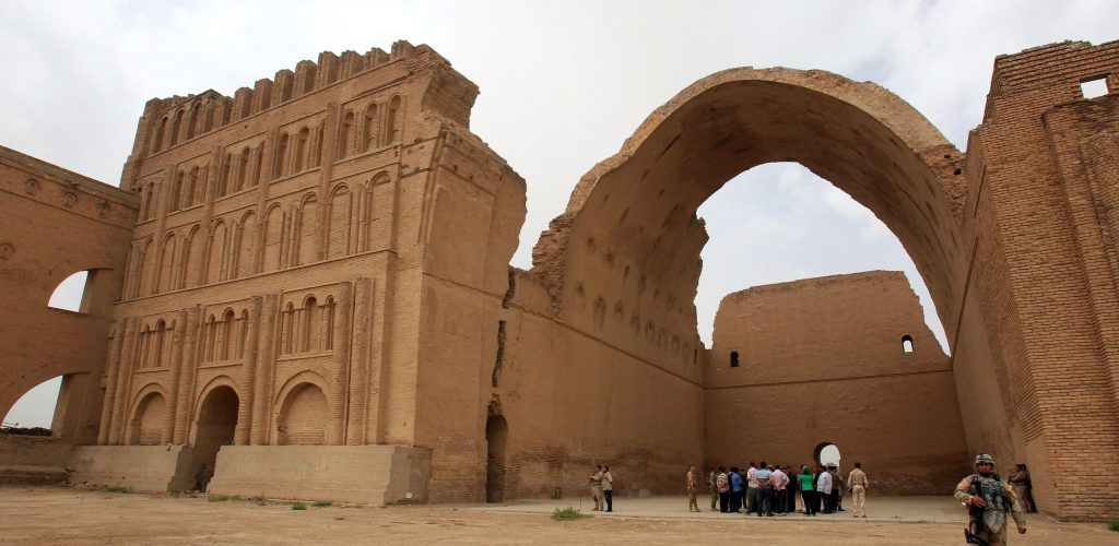 TO GO WITH AFP STORY BY MOHAMAD ALI HARISSI - Iraqis stand under the arch of the barrel-vaulted hall of the Ctesiphon palace, which was in the imperial capital of the Persian Empire in the Parthian and Sassanian times, near Madean, 30 kilometres south of Baghdad, on May 15, 2013. A foreign company is planning a project to stabilize the arch which has a span of more than 80 feet, and reaches a height of 118 feet, after parts of it began to crumble.  AFP PHOTO / ALI AL-SAADI